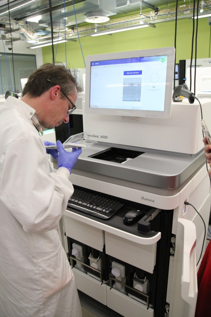 NovaSeq DNA sequencing machine being loaded with 56 people's genomes