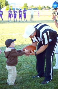 Dallas Peterson, 3, who was recently diagnosed with leukemia, delivered the game ball to the official prior to kick-off at the 2016 Gunnison Valley High Homecoming game. - Tiffanie Jackson / Messenger photo