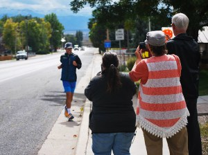 Don Stewart (left), Terry Madsen and Kim Roy snap a photo to commemorate the arrival of champion ultramarathon runner Pete Kostelnick as he travels through Fairview during  an attempt to set a Guinness world record. Kostelnick is attempting to run 3,100 miles from San Francisco to New York City in 44 consecutive days.