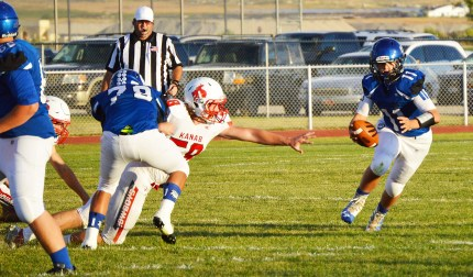 Gunnison Valley High's varsity quarterback Kris Edwards jukes away from the reach of a Kanab athlete when the two teams clashed on Friday. Although the Bulldogs fought hard, it ended with Kanab taking a 37-12 victory over the blue and white.