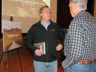 Joel Warren, a Geographic Information Systems (GIS) consultant for Jones and Demille Engineering, talks with a visitor at an open house on a Sanpete Resource Management Plan now being developed. The open house was held Nov. 10 at the Peterson Dance Hall in Fairview.