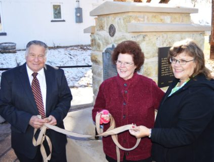 Spring City Mayor Jack Monnett (left) and Spring City DUP members Carla Nelson (center) and Cherrie Barrow participate in the ribbon cutting at the rededication ceremony for the newly restored historic DUP monument on Main Street in Spring City.