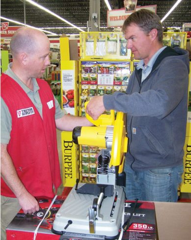 Daniel Kjar, working at Tractor Supply in Ephraim, helps Garrick Willden of Mayfield with question on operation of saw.