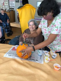 Resident and staff decorating a pumpkin