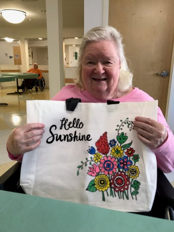female San Simeon resident holding up painted tote bag