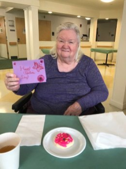 San Simeon female resident holding up Valentine's Day card