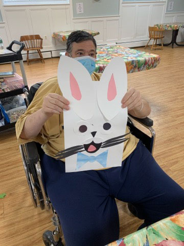 male San Simeon resident holding up Easter bunny art