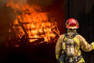 Fireman looking at burning house
