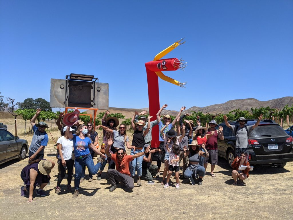 Permaculture design course students build community by waving their hands together while touring a broadscale permaculture site.