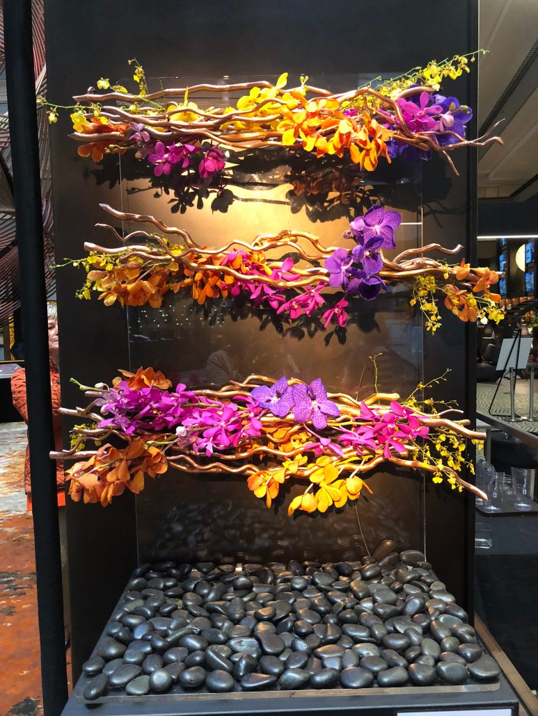 Three seemingly suspended layers of florals and branches twisted together in fuchsia, gold, and violet.