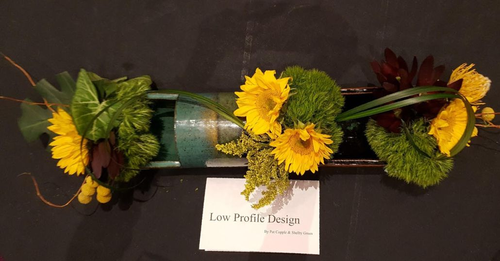 Horizontal shaped ceramic holds bright sunflowers and green accents.
