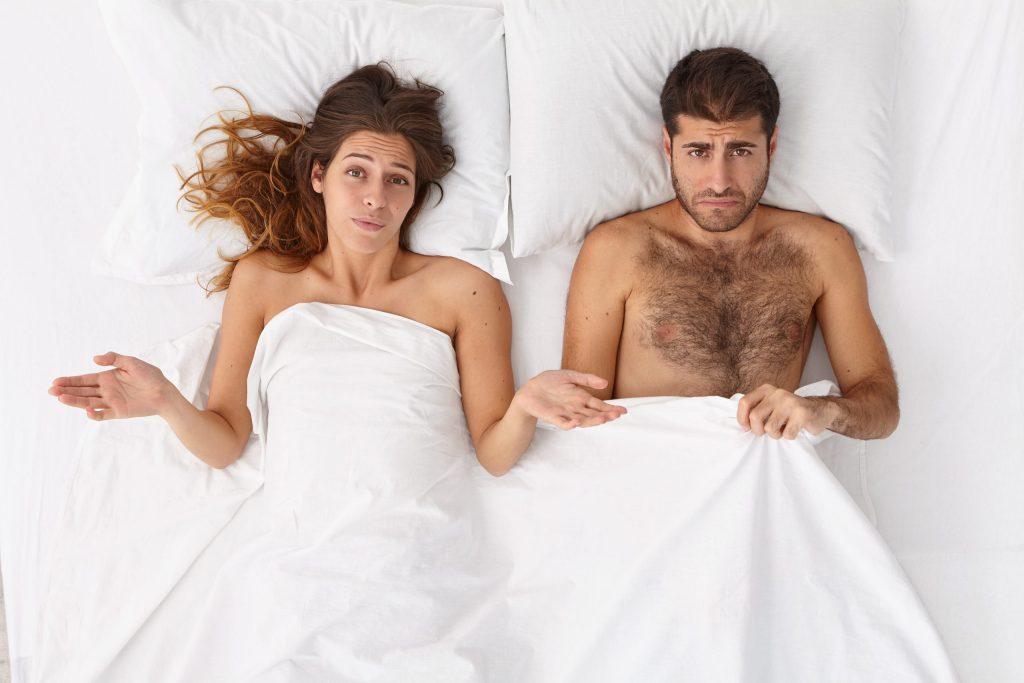 Couple au lit qui sont dubitatif