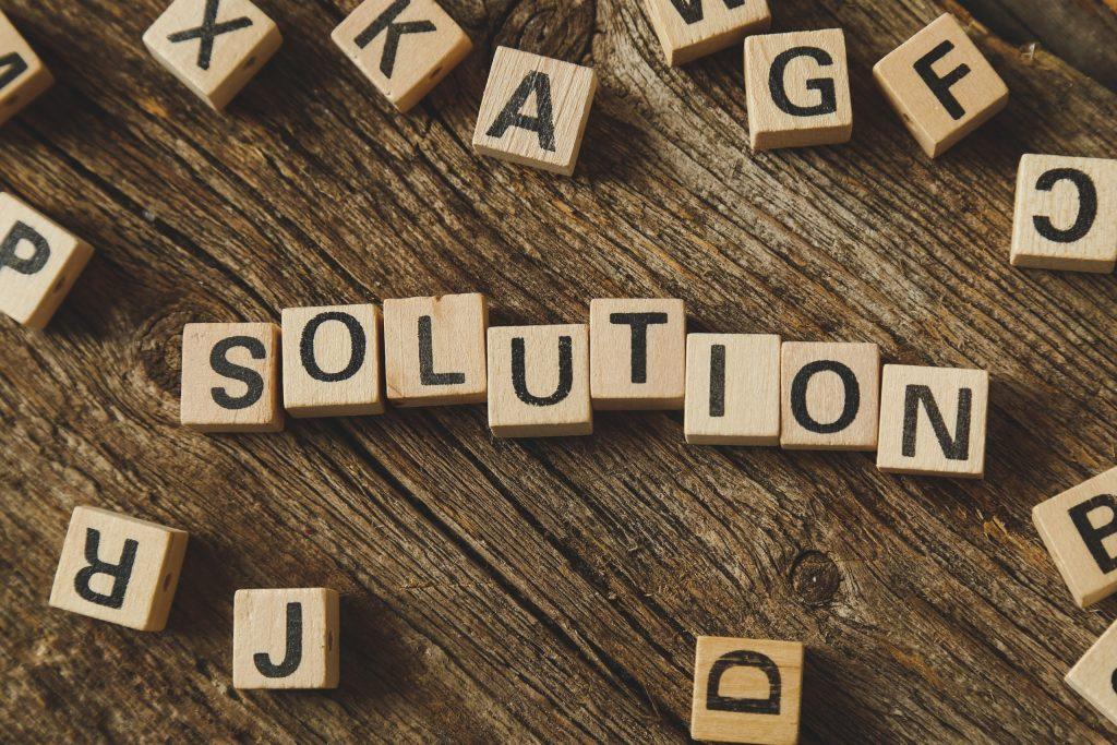 Photographie de lettre du scrabble qui forment le mot : solution