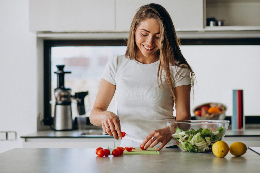 Jeune femme debout qui coupe quelques légumes sur son plan de travail