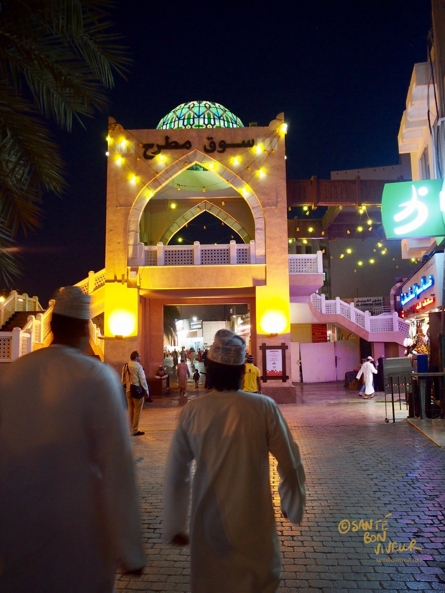 Men in everyday Omani dress approach Mutrah Souq, Muscat from the Corniche