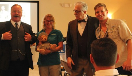 Teddy Roosevelt reprisor Joe Wiegand (left) along with Darling reprisor Tom Milligan presented Wendy Schnapp and Adam Sauerland, representatives from Tarpon Bay Explorers, the refuge's recreation concession, with a Teddy bear for their good work.