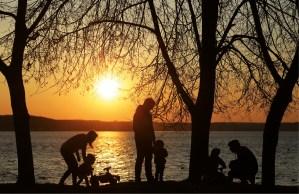 Pais e filhos. Pôr do sol junto ao lago.