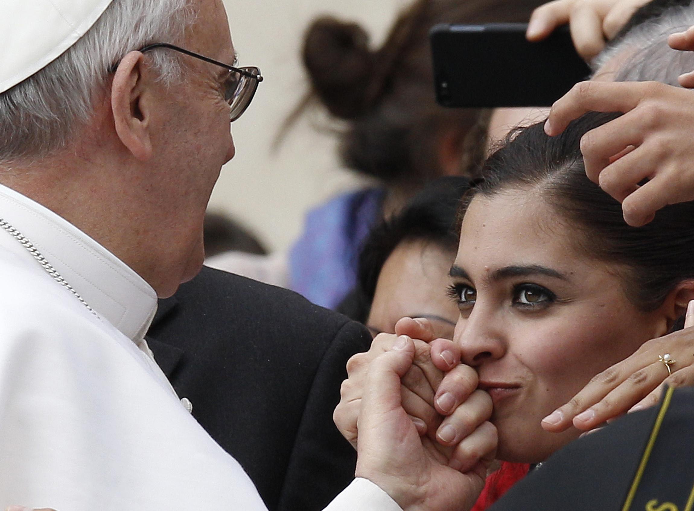 Mulher beija a mão do papa Francisco durante a audiência geral na Praça de São Pedro no Vaticano. Foto/Paul Haring, Março, 2013