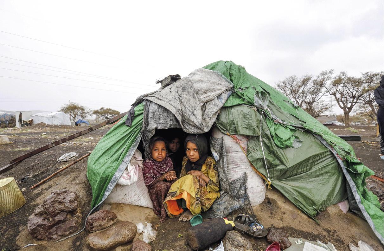 Crianças iemenitas protegem-se da chuva num abrigo improvisado num acampamento para deslocados na província de Amran, no norte do Iémen, vítimas de um conflito que se arrasta há três anos. 18 de abril de 2018, EPA / YAHYA ARHAB.