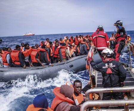 Refugiados, num bote de borracha, sendo resgatados por membros da ONG SOS Mediterranée do navio Aquarius, 18 de abril de 2018. EPA / CHRISTOPHE PETIT TESSON.