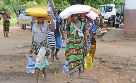 Mulheres transportam comida e água distribuídas pela Helpo, na aldeia Sunate, após a passagem do Ciclone Kenneth, no distrito de Pemba, norte de Moçambique, 29 de abril de 2019. A tempestade matou 41 pessoas, de acordo com o levantamento provisório das autoridades e afetou cerca de 166 000 pessoas. Foto EPA / ANTONIO SILVA.