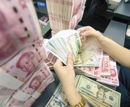 O colonialismo do deus-dinheiro. Funcionária conta as notas numa agencia bancária de Jiangsu, na China, Foto EPA / Xu Jinbai.