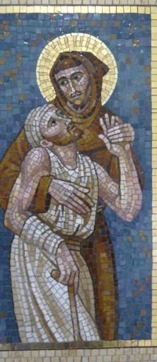 São Francisco e o leproso. Mosaico na Cúria Geral da OFM. Foto de Jim McIntosh, commons.wikimedia.org.