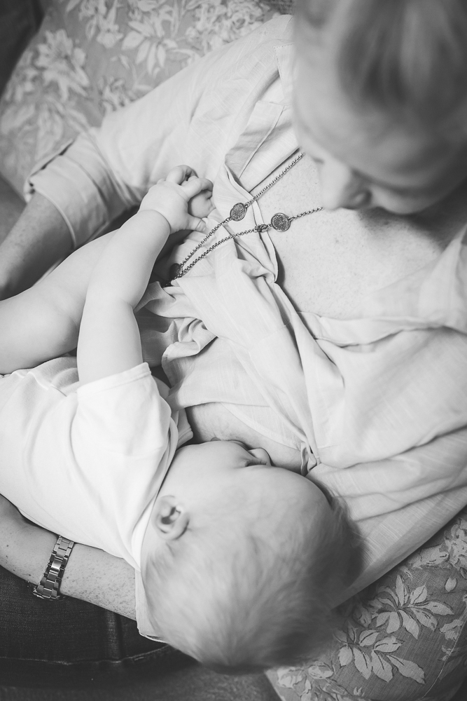 baby plays with his toes while breastfeeding