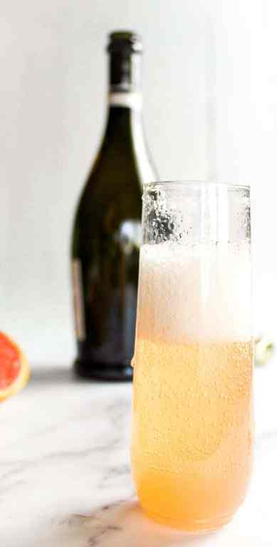 grapefruit elderflower cocktail poured into a stemless champagne flute
