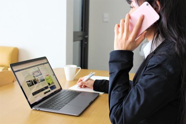 パソコンの前でスマホを耳にあてている女性