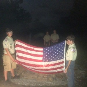 Eagle Scout Kaden Jackson on left instructing Tenderfoot Scout Joshua VandeVenter on flag retirement. First Class Scout Nick Lynam and Life Scout Nickey Cooper watch from the background.