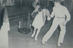 One skater falls while two scurry out of the way at Dixieland Roller Rink. The rink was destroyed by fire sometime after the 1950s.
