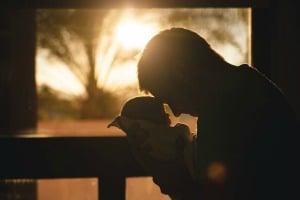 Sara Grillo - Man holding a newborn in silhouette