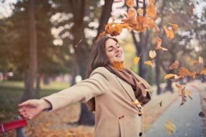 Sara Grillo - Woman dancing in fall leaves