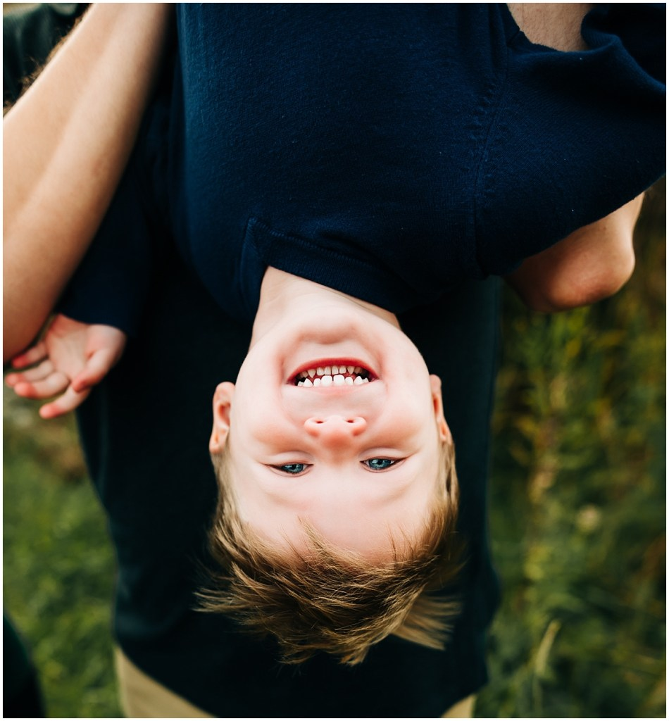 Boy hanging upside down laughing