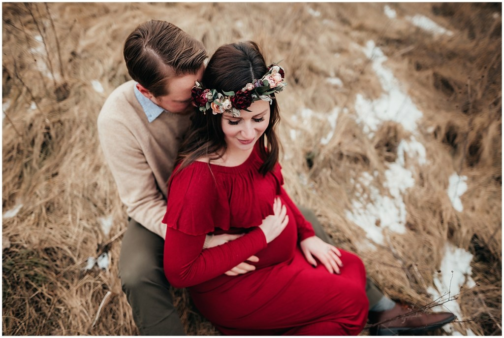 Brighton Michigan maternity photo of couple sitting on the ground with snow
