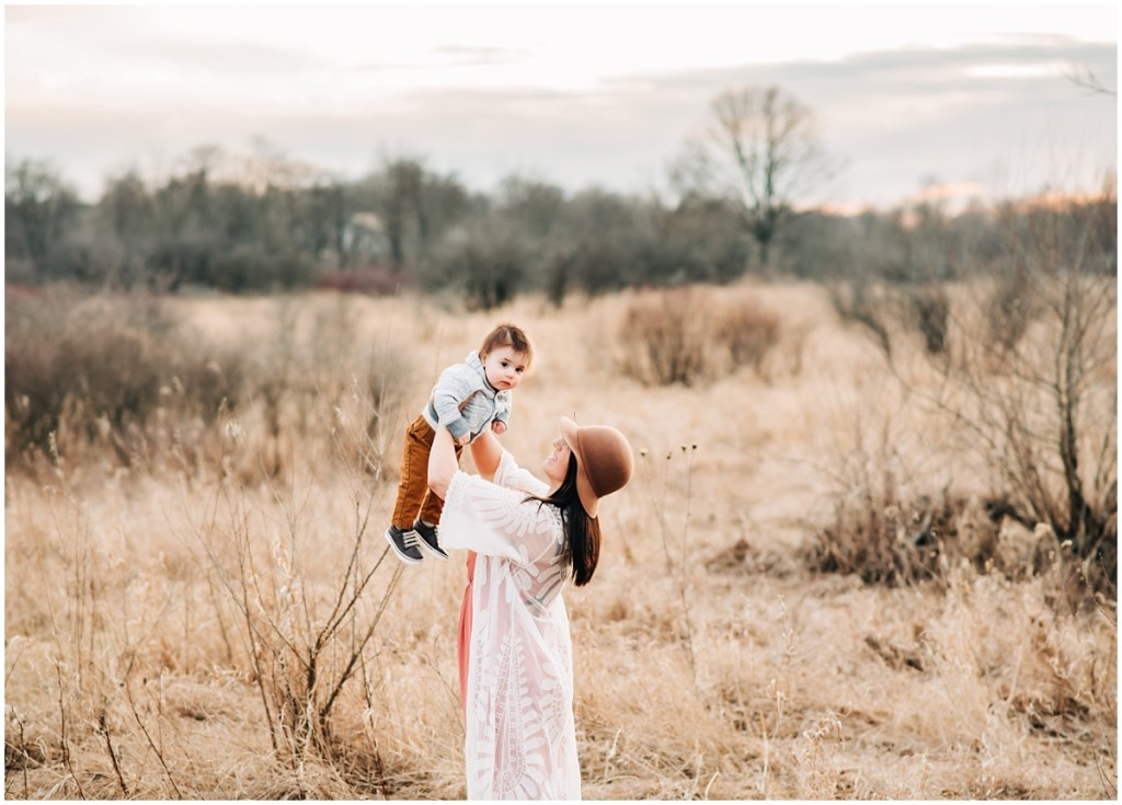 Mom throwing son in the sky outside for a picture outdoors in a field in Ann Arbor.