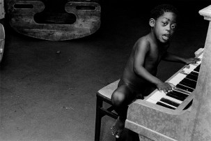 Boy playing the piano at an adventure playground for children with disabilities, London.