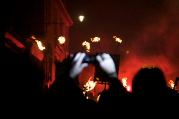 Hands taking a photo, Lewes Bonfire parade, Sussex, 2010