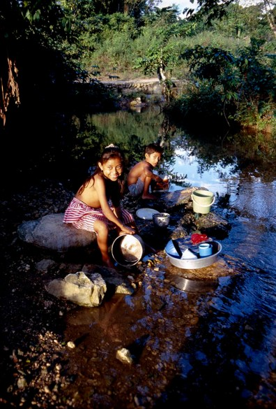 Children washing crockery in the stream, San Jose, Belize