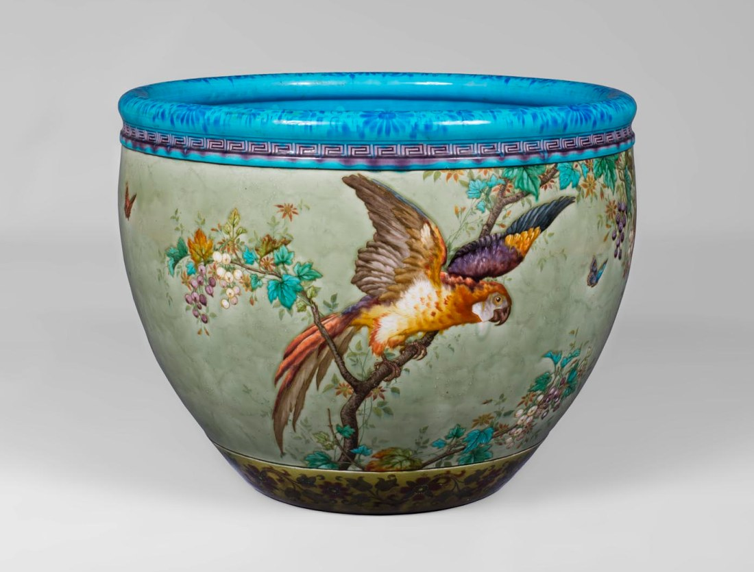 Glazed ceramic cachepot with a parrot and butterflies.