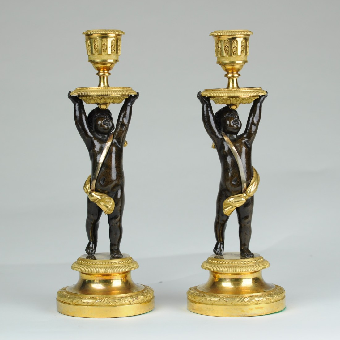 Candlesticks in the form of putti standing on gilt bronze plinths and supporting foliate candle sconces. 1820. Regency in style.