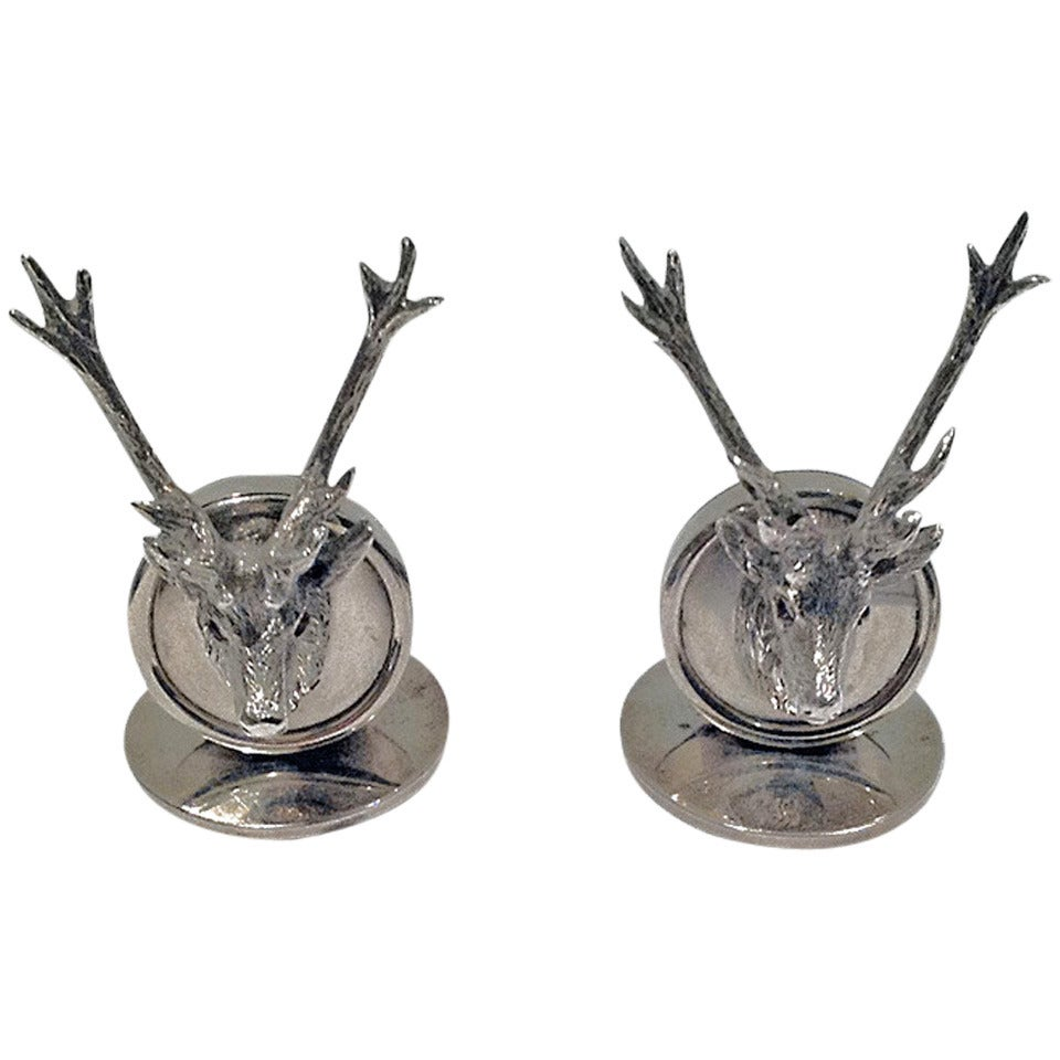 Stag menu place card holders. Disc shape, surmounted by a stag's head inset with cabochon red eyes.
