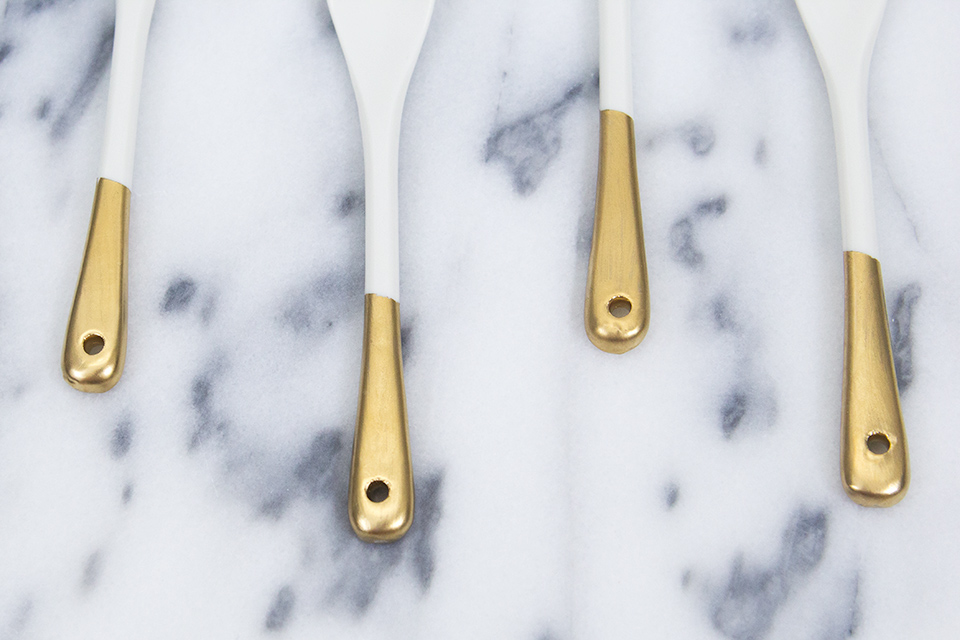 Inexpensive white porcelain spoons get a makeover with metallic gold paint.