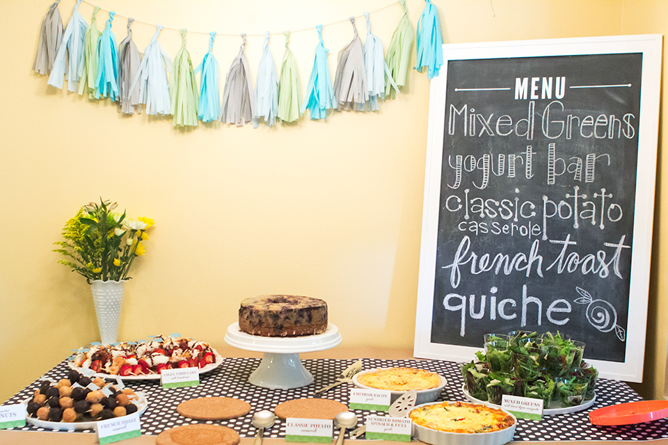 A sweet and simple baby shower brunch buffet. Love the big chalkboard menu and tassel garland.