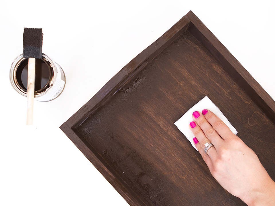 Use a paper towel to remove excess wood stain immediately after applying it. Click through to see the full polka dot tray tutorial.