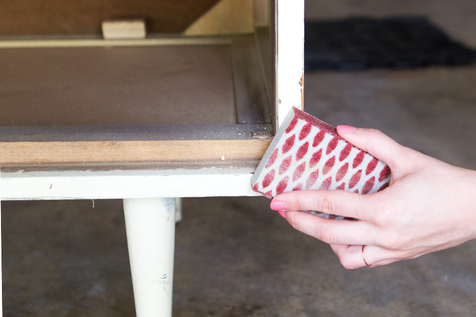 Use a 60 grit coarse sand paper to remove any paint or other residue from an old furniture piece.