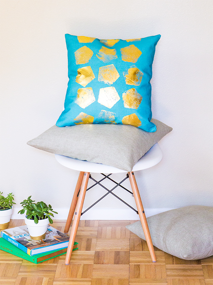 Love this pretty throw pillow! Learn how to spruce up a plain throw pillow cover using gold foil. (Click through for tutorial)