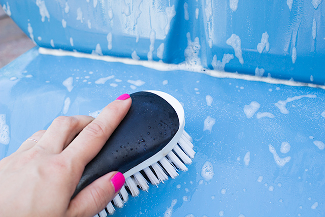 Use a nylon scrub brush to clean metal furniture without scratching the paint.