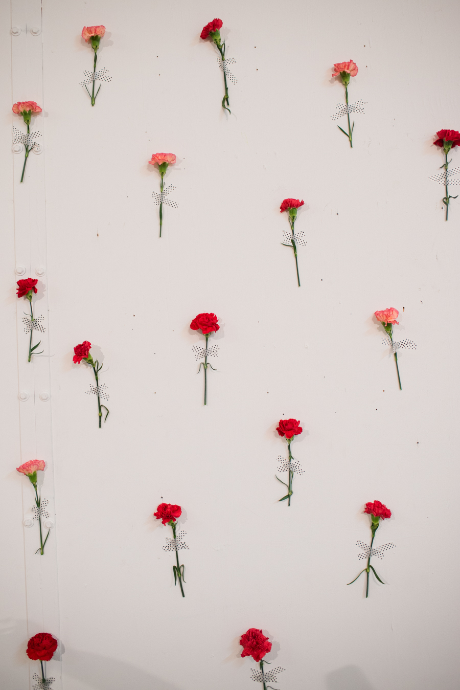Use washi tape to adhere fresh flower stems to create a beautiful backdrop that's perfect for photo booths, dessert tables or even a wedding ceremony.